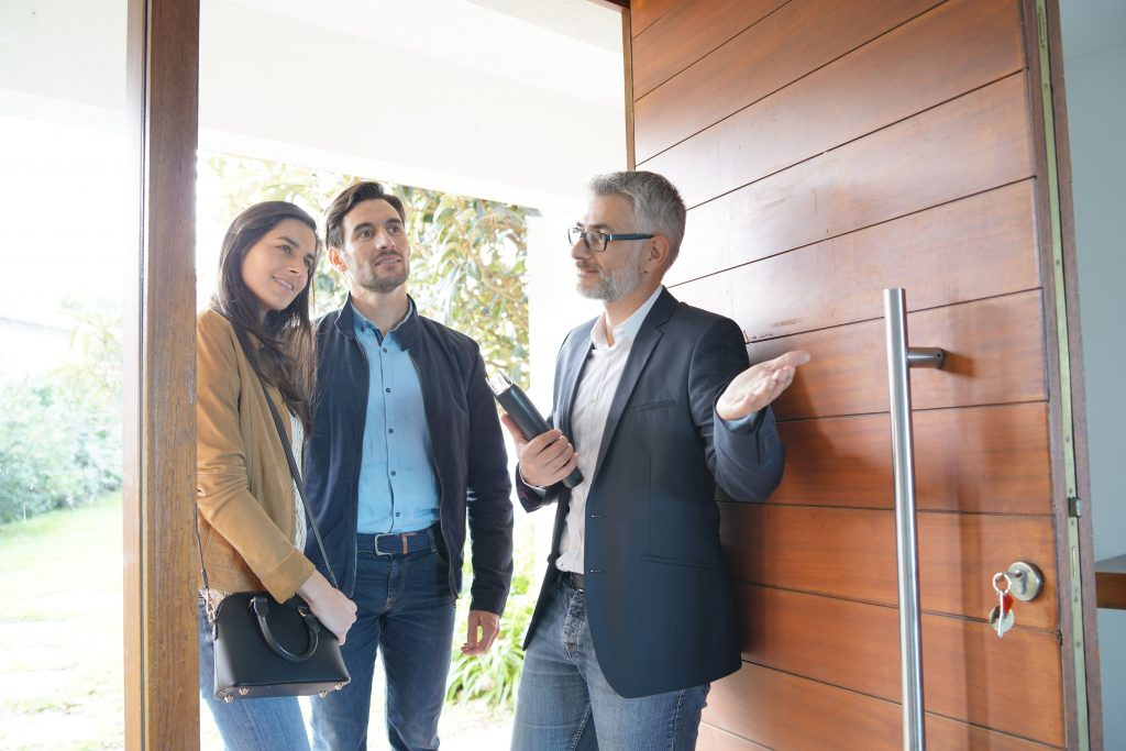 Couple With Real Estate Agent Visiting Modern House